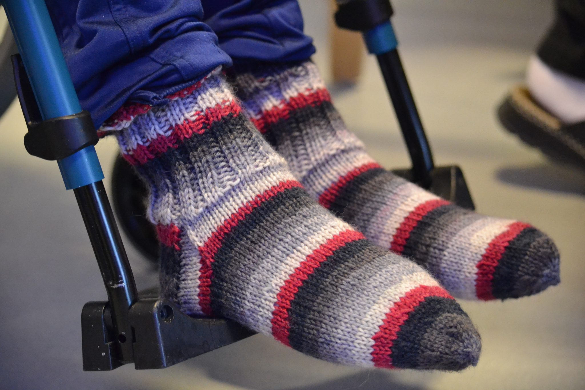 Toinin varpaat läpiävät raidallisissa sukissa.
