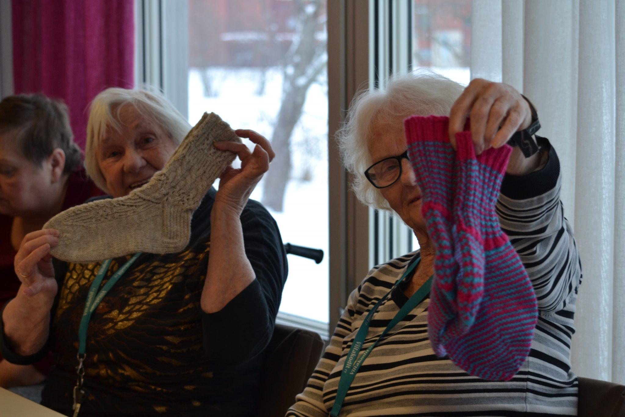 Leena ja Raili esittelevät ylpeinä villaisia sukkiaan